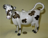 Grey cow creamer with black marks, crazing, and no base