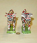 Two red and black splatter painted cow creamers on green bases, front