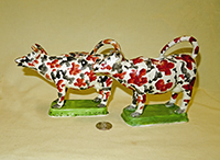 Two red and black splatter painted cow creamers on green bases, side