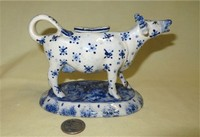 Cow creamer with blue decorations and long neck, with stapled repairs