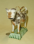 orange and brown sponged prattware cow on light green base, incised lid with hoop, front