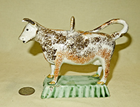 orange and brown sponged prattware cow on light green base, incised lid tith hoop, side