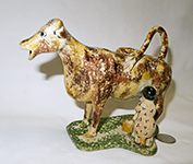 Brown and yellow early 1800s English cow creamer with milkmaid