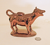 Copper lustre cow creamer on base