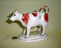 White cow creamer with brown spots and gold horns