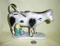 White & black cow creamer with milkmaid