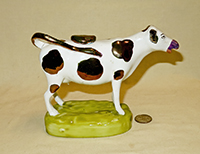 Bronze lustre nosed and spotted Swansea cow creamer on tall light green base