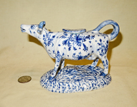 Long necked cow creamer with blue flowers, left
