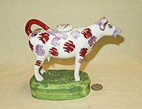 Purple nosed Swansea cow creamer on tall green base