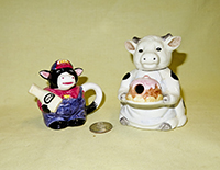 Miniature cow teapots, a farmer and a lady with a cake