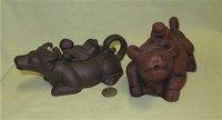 Two Chinese clay water buffalo teapots with boys on lids