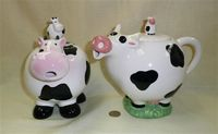Two spherical cow teapots with calves on lids