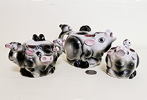 Small grey cow teaset with heads on handle