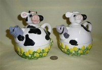 Two similar tea for one cow teapots with cups