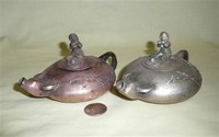 Two Chinese flatish metal water buffalo teapots with boys playing flutes on top