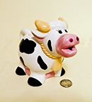 small cow teapot with pink nose and big yellow horns