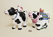 Two black and white cow teapots with birds on lids
