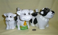 Three thick ceramic cow teapots with cold paint